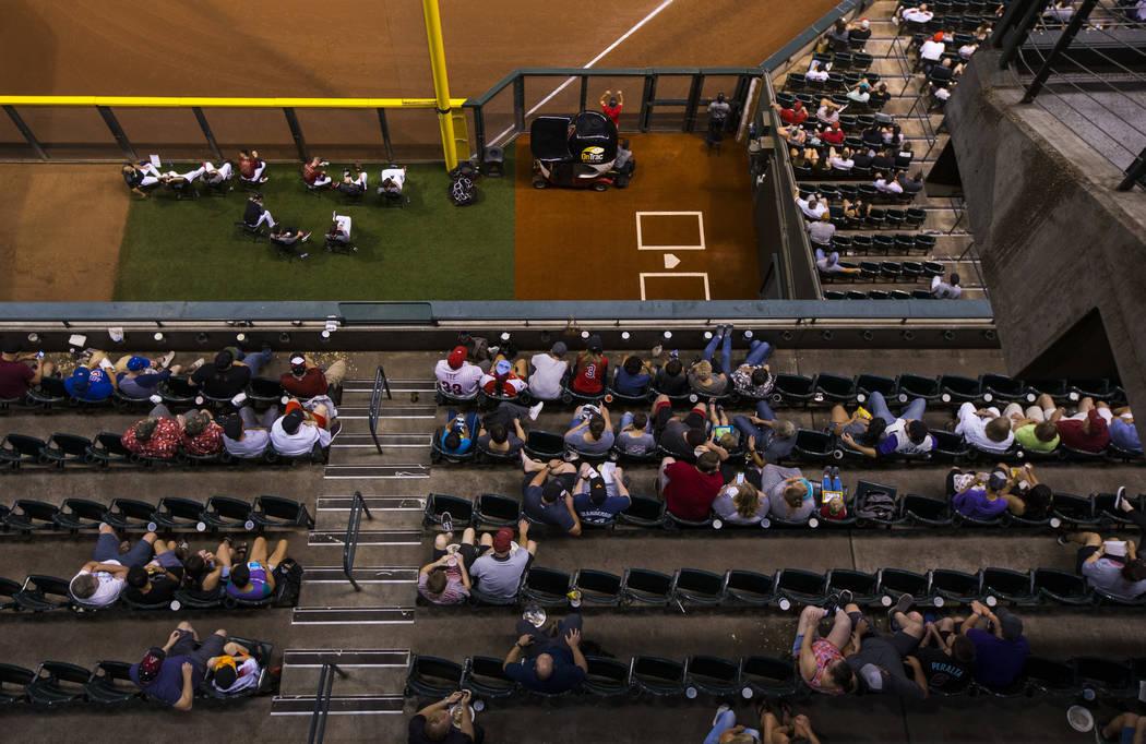 Fans miran la acción durante un partido de béisbol de los Diamondbacks de Arizona contra los ...