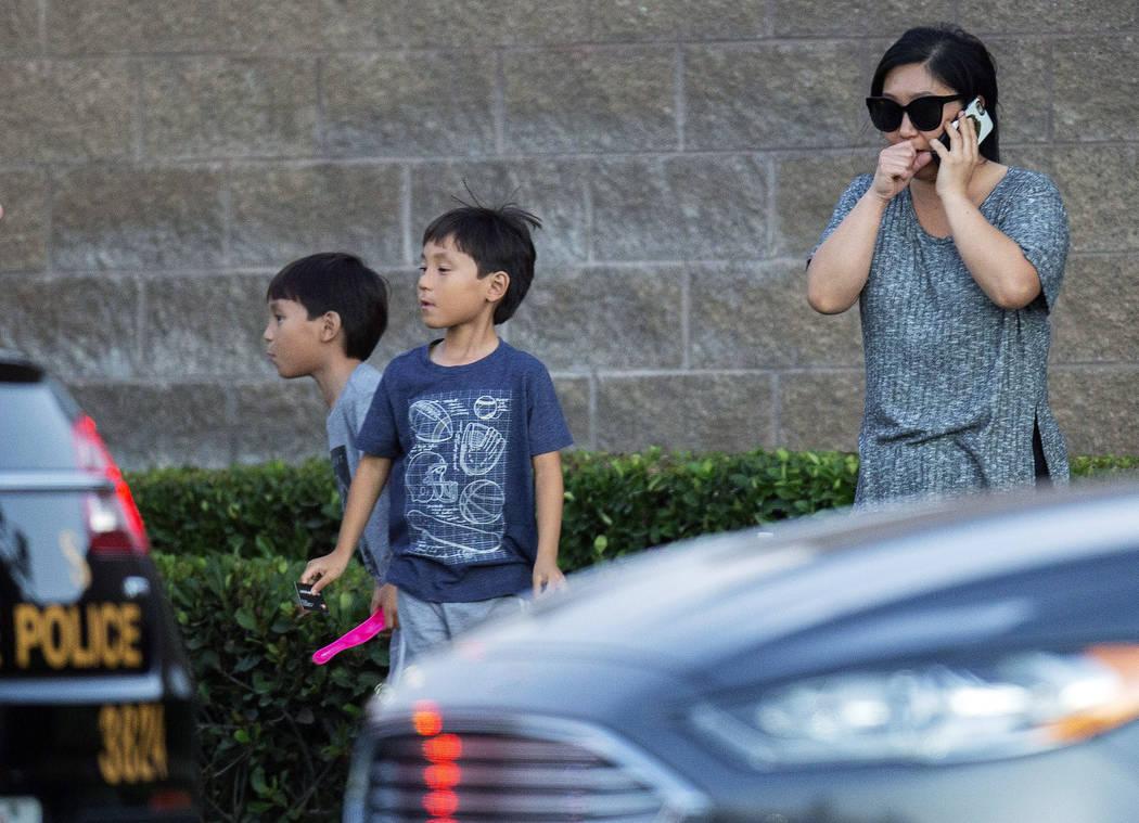 Una mujer y sus dos hijos se encuentran cerca de la escena donde un tiroteo cerca de una autopi ...
