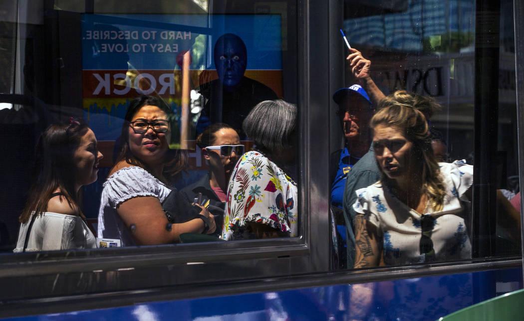 Pasajeros reflejados en las ventanas de un autobús de la RTC cuando suben al autobús cerca de ...