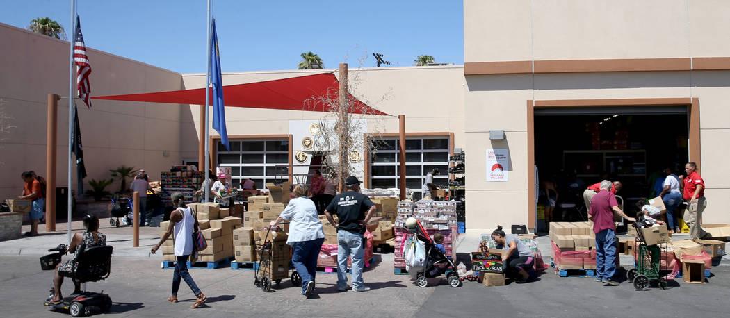 Personas recogen comida durante la distribución de un banco de alimentos en Veterans Village e ...