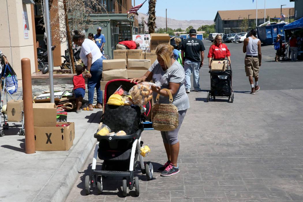Carina López recoge comida durante una distribución del banco de alimentos en Veterans Villag ...