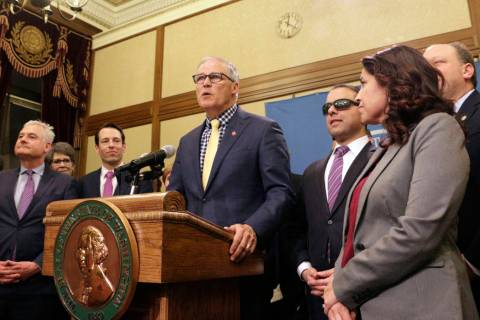 ARCHIVO - En esta foto de archivo del 29 de abril de 2019, el gobernador Jay Inslee, rodeado de ...