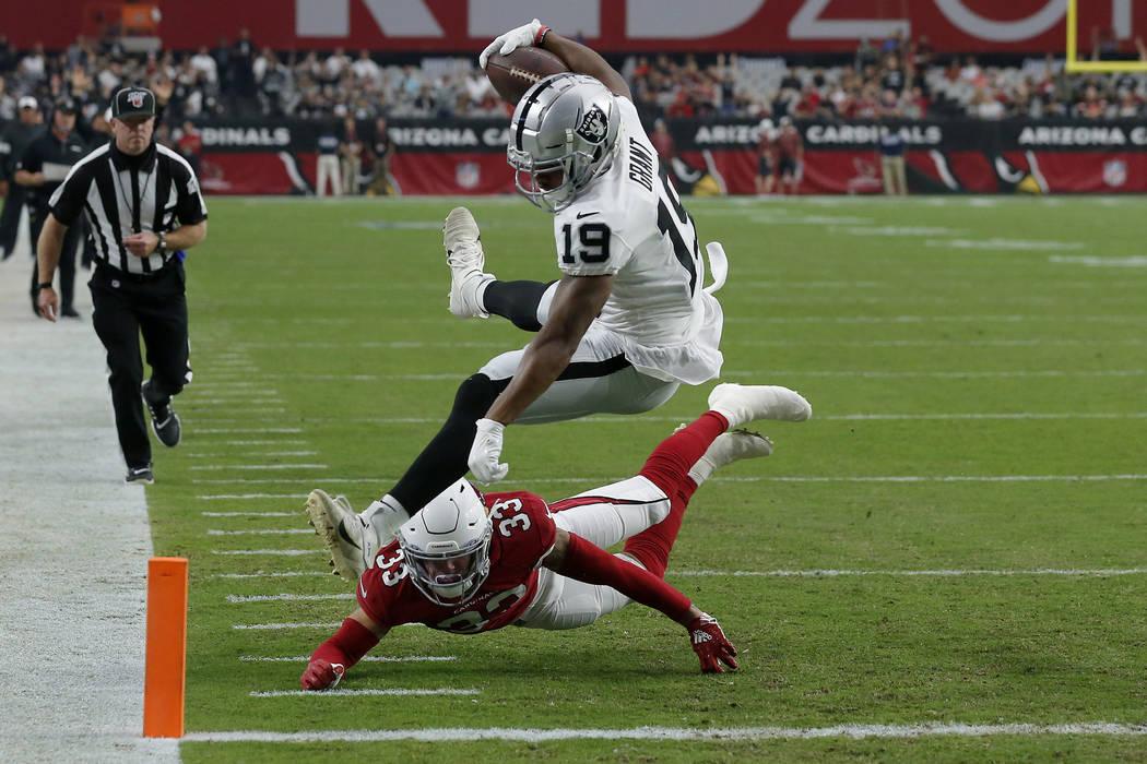 El receptor abierto de los Oakland Raiders, Ryan Grant (19), anota un touchdown mientras el esq ...