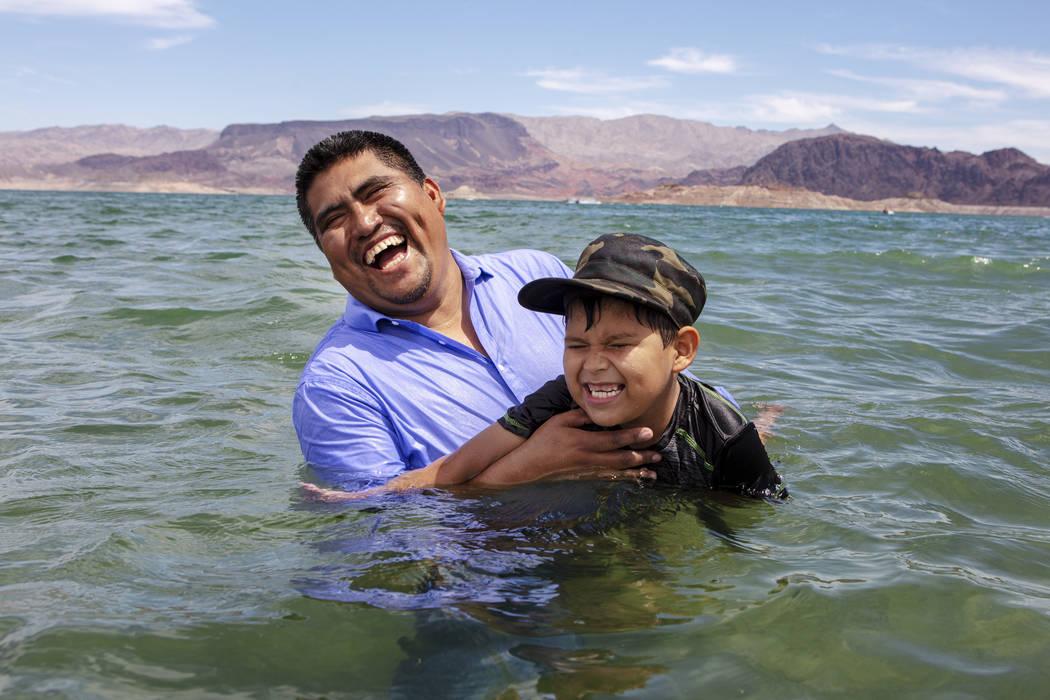 El pastor Erasmo Solis se ríe mientras enseña a su hijo, Girsom Solis, a nadar en Boulder Bea ...