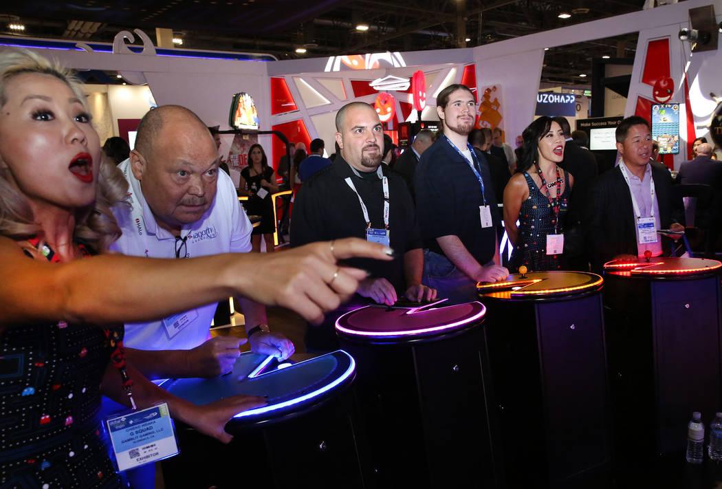 Chieko Hidaka, a la izquierda, de Gamblit Gaming, reacciona mientras asistentes a la exposició ...