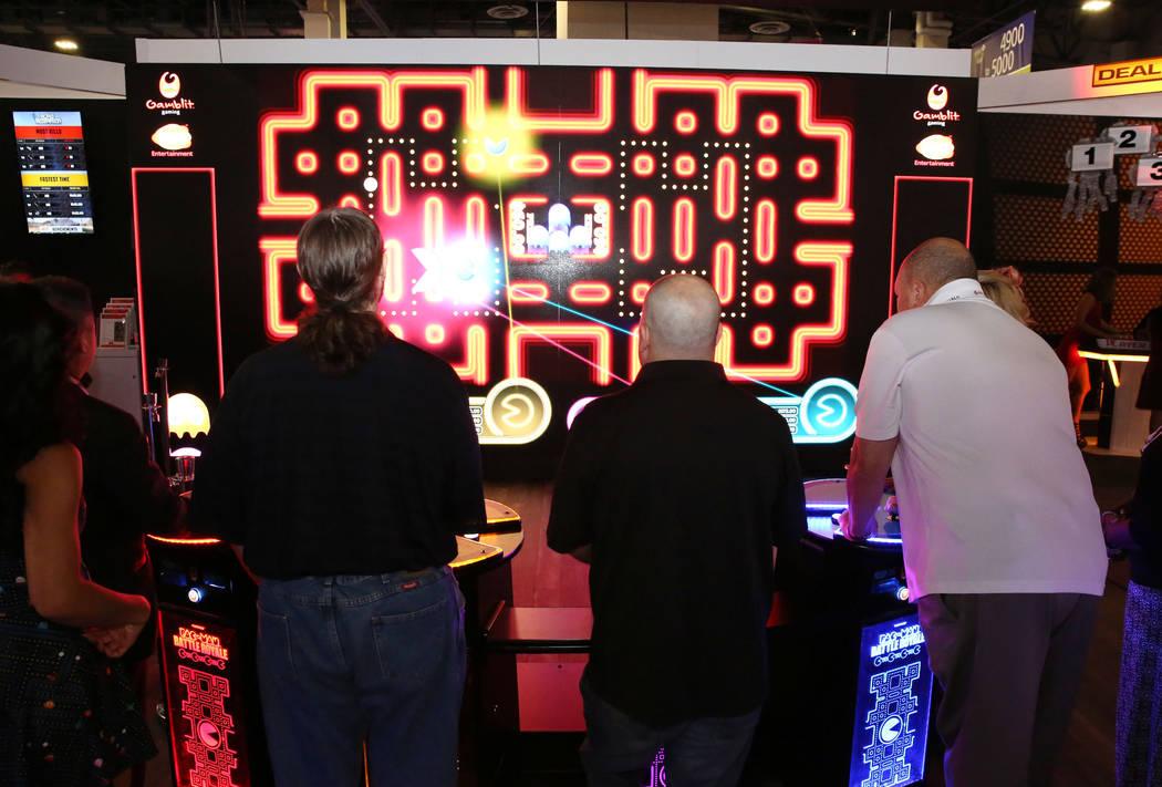 Asistentes juegan Pac-Man Battle en el stand de Gamblit Gaming durante la Global Gaming Expo en ...