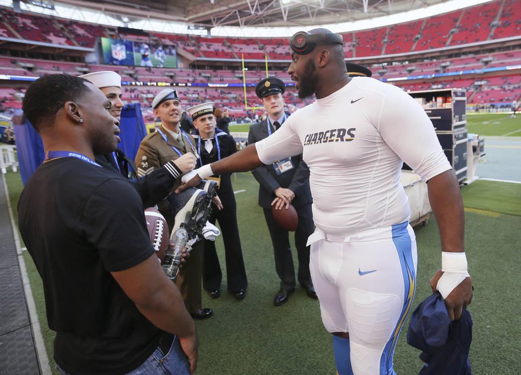 El tackle defensivo de Los Angeles Chargers, Corey Liuget, saluda al personal militar antes de ...