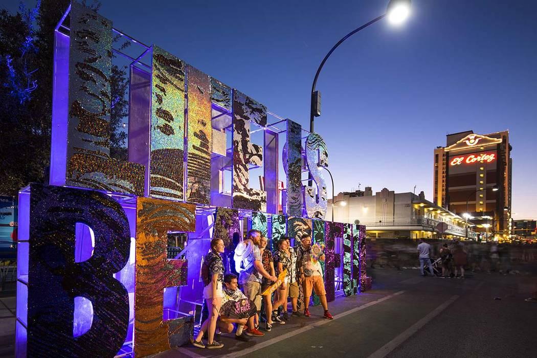 Los asistentes al festival posan junto a un cartel de Life is Beautiful en el festival anual en ...