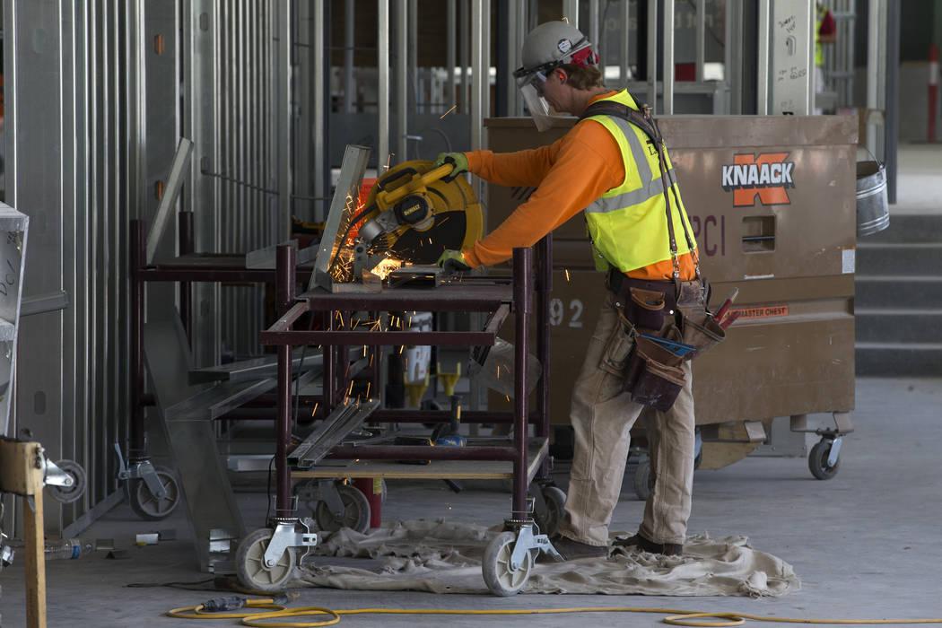 Un trabajador corta una pieza de metal en el sitio de construcción del estadio Raiders Allegia ...