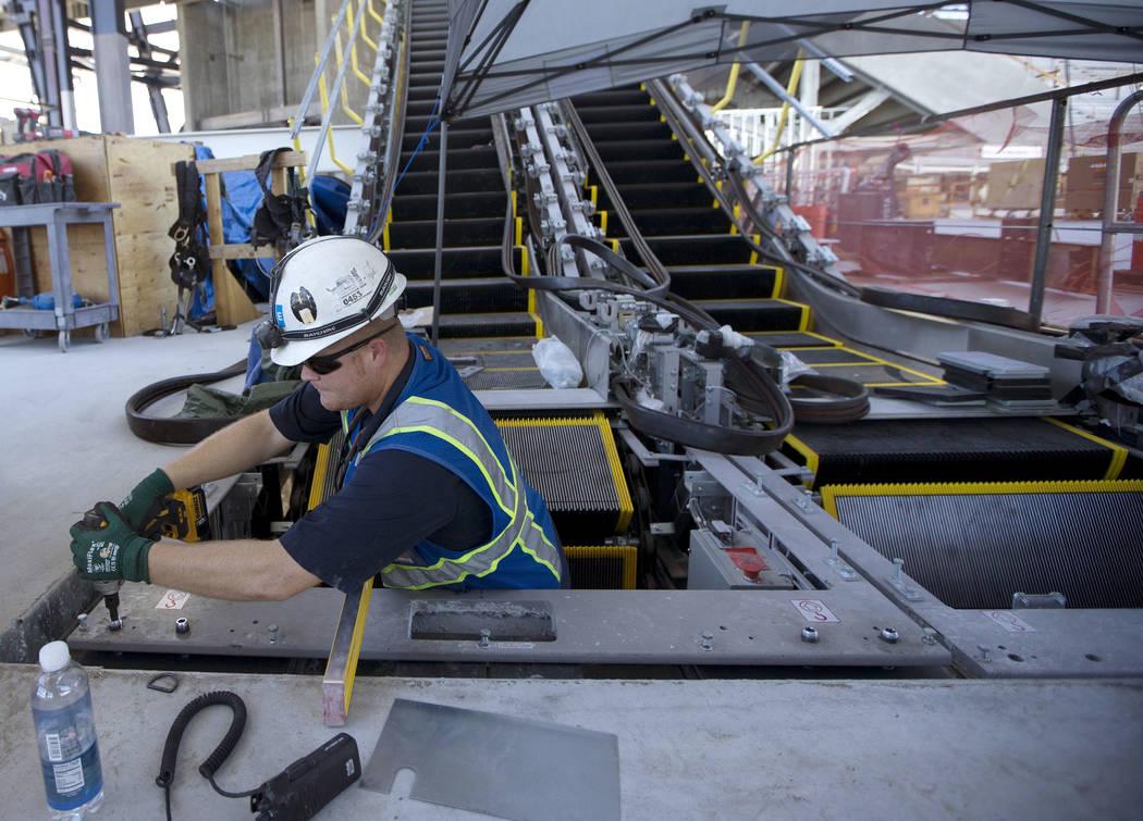 El capataz de escaleras mecánicas Cory Johnston trabaja en las escaleras mecánicas recién in ...