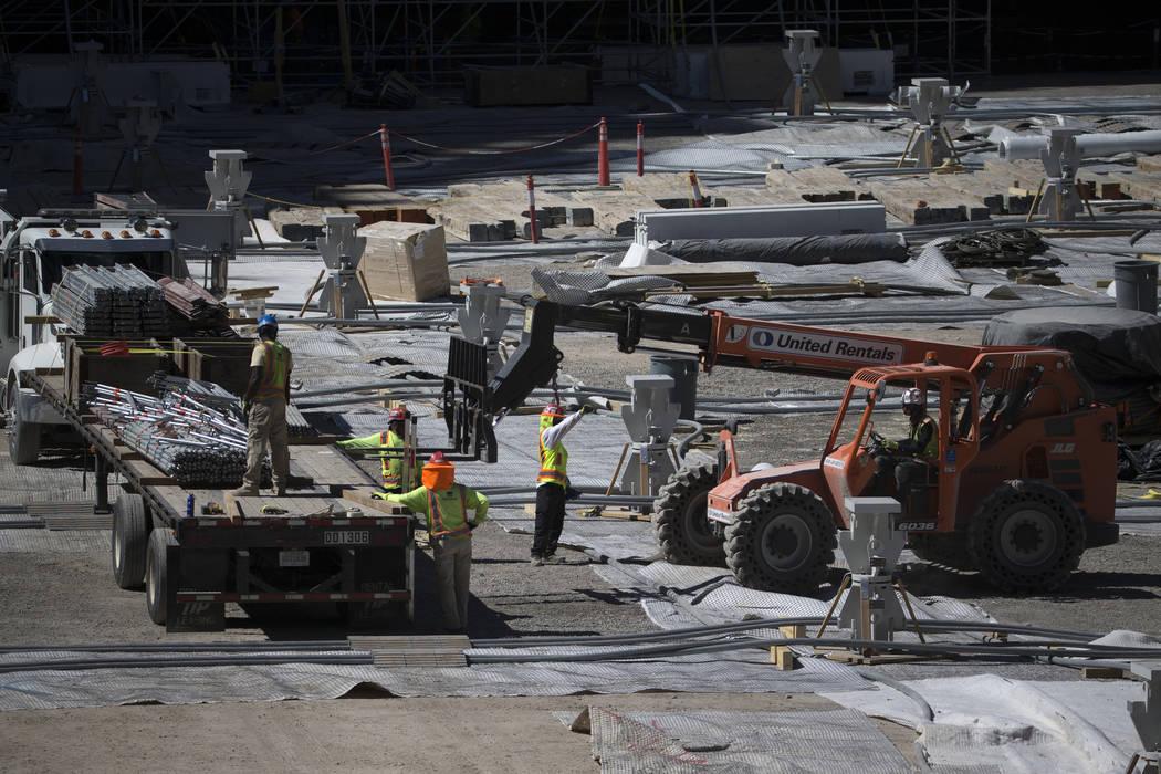 Los trabajadores mueven el equipo desde el nivel del piso del sitio de construcción del estadi ...
