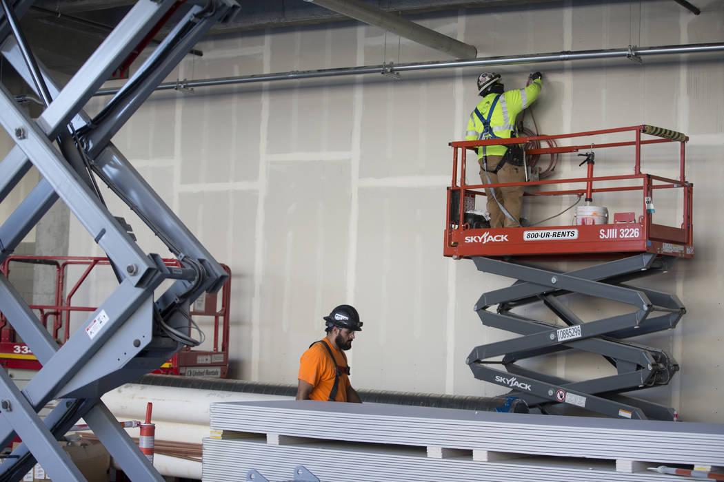 Un trabajador, a la derecha, parcha una pared en el sitio de construcción del estadio Raiders ...