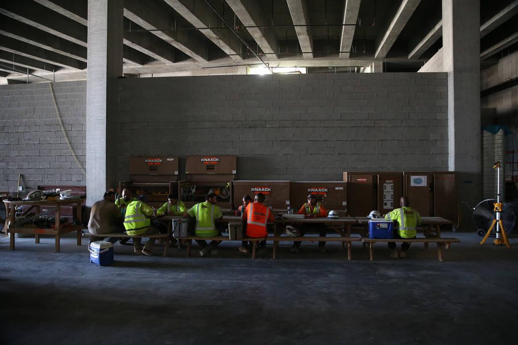 Trabajadores se sientan para almorzar en el sitio de construcción del estadio Raiders Allegian ...