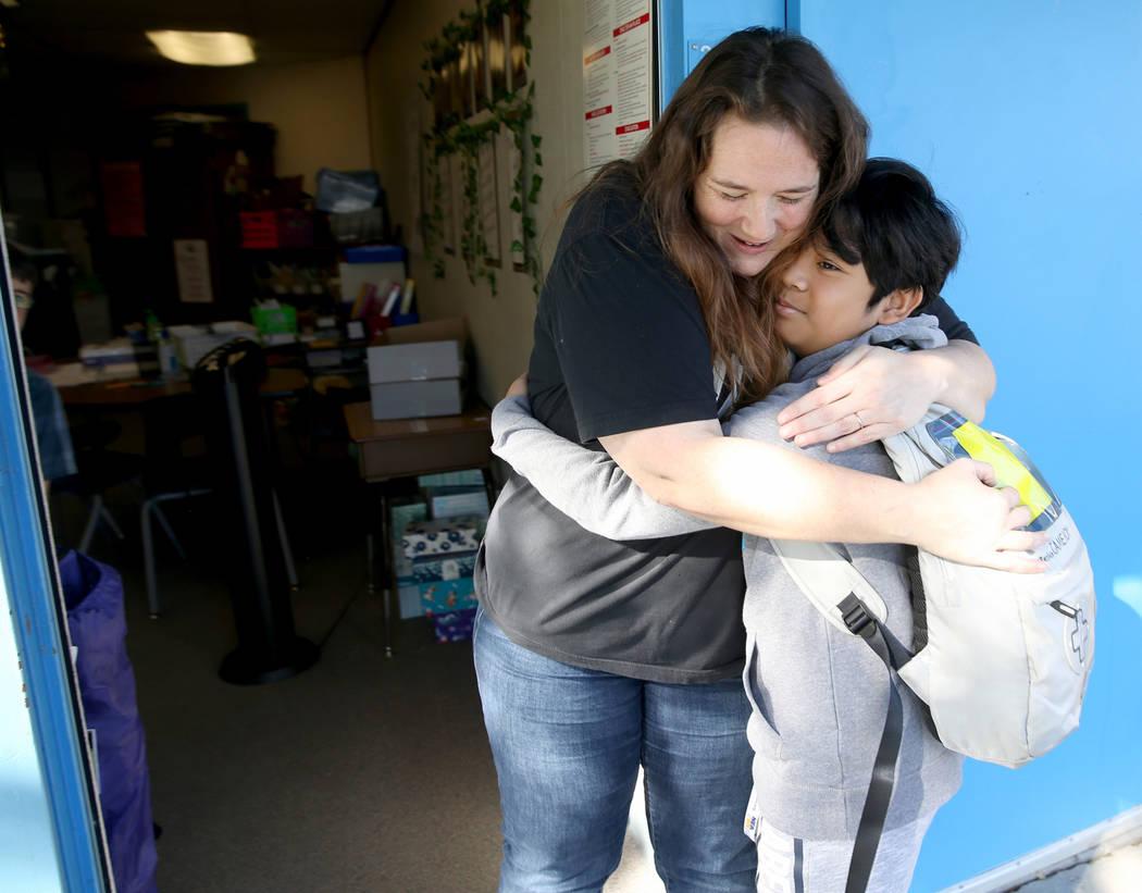 La maestra de cuarto grado de la Escuela Primaria Helen Smith, Sarah Sunnasy, recibe un abrazo ...