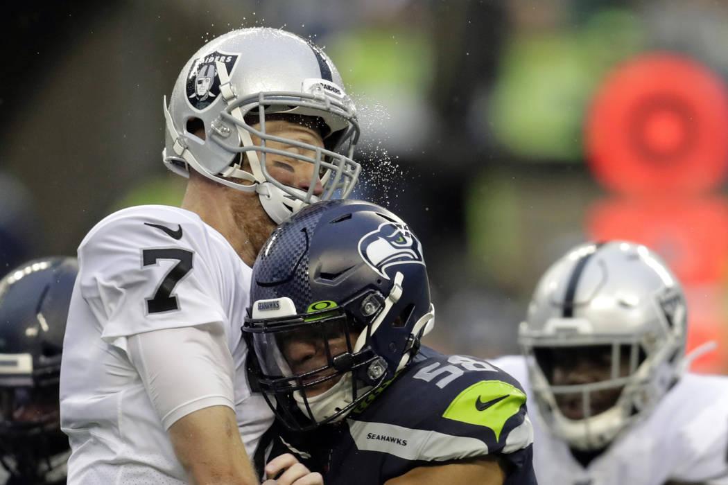Lluvia salpica mientras el mariscal de campo de los Oakland Raiders, Mike Glennon, a la izquier ...