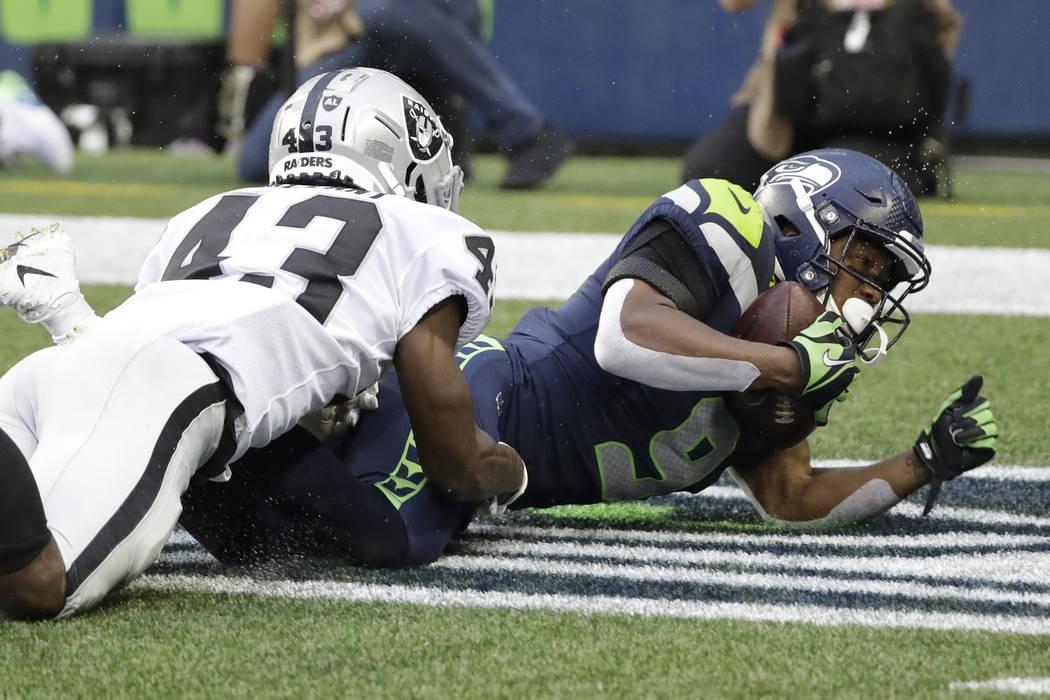 El receptor abierto de los Seattle Seahawks, Terry Wright, a la derecha, desciende cuando el es ...