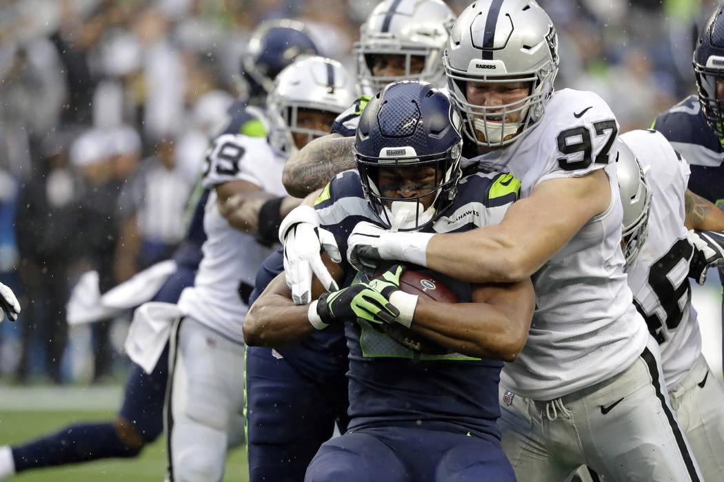 El corredor de los Seattle Seahawks, C.J. Prosise, en el centro, es noqueado por el ala defensi ...