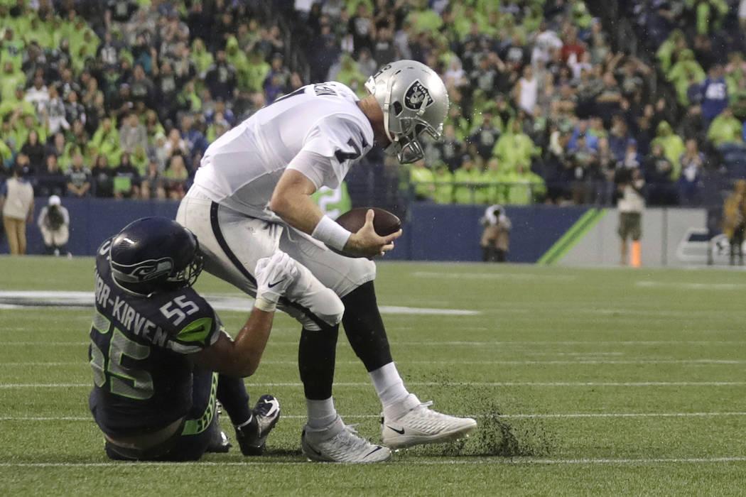 El apoyador de los Seattle Seahawks, Ben Burr-Kirven (55), saquea al mariscal de campo de los O ...