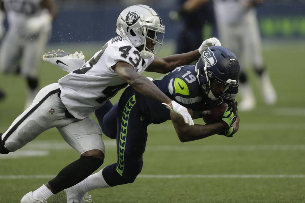 El esquinero de los Oakland Raiders, Makinton Dorleant (43), aborda al receptor abierto Keenan ...