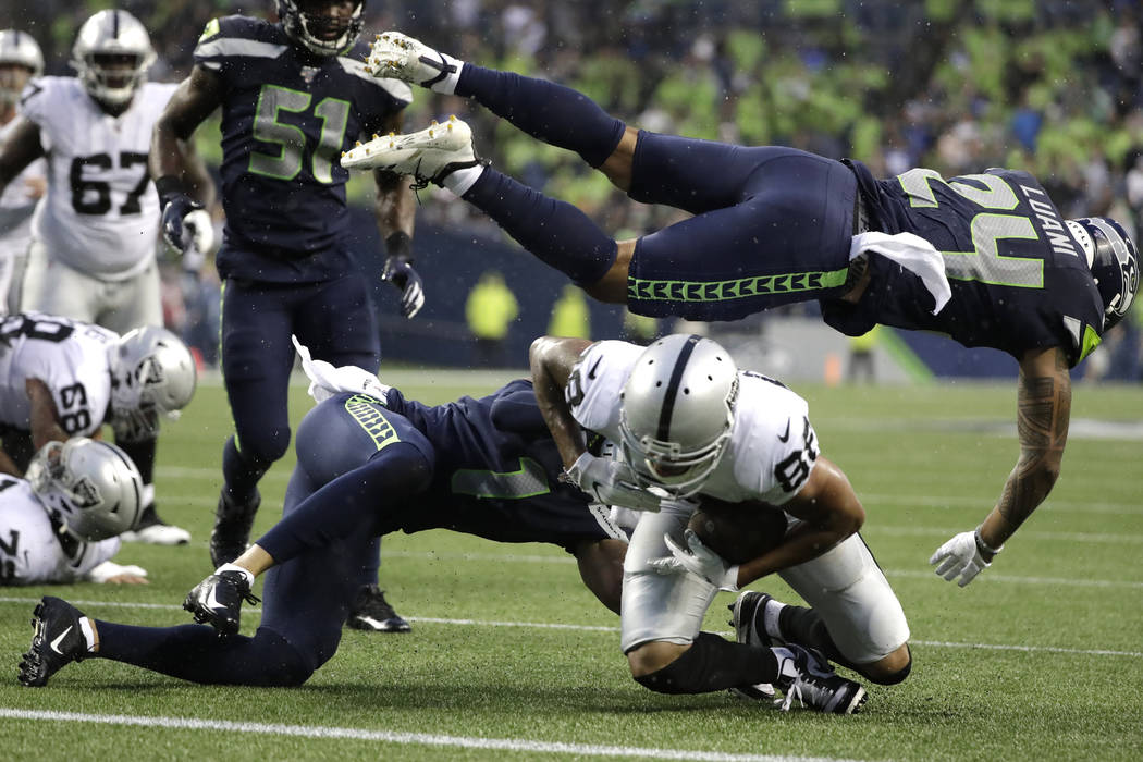 El defensa de los Seahawks de Seattle, Shalom Luani (24), vuela sobre el receptor abierto de lo ...