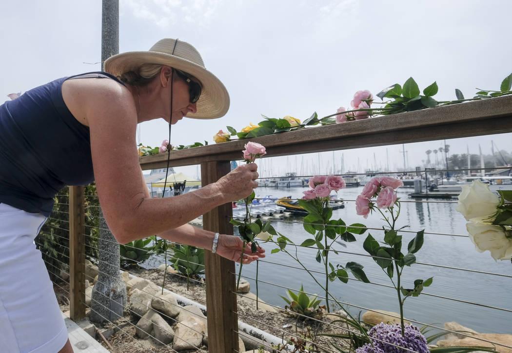 Maya Upton, de Santa Bárbara, California, coloca flores en las afueras de Sea Landing en el pu ...