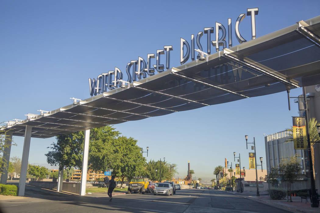 Un peatón cruza debajo de un letrero que identifica el icónico distrito de Water Street en So ...