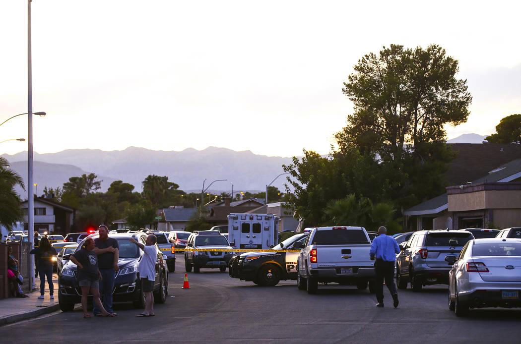 La policía de Las Vegas asegura el área alrededor de una calle residencial mientras esperan u ...