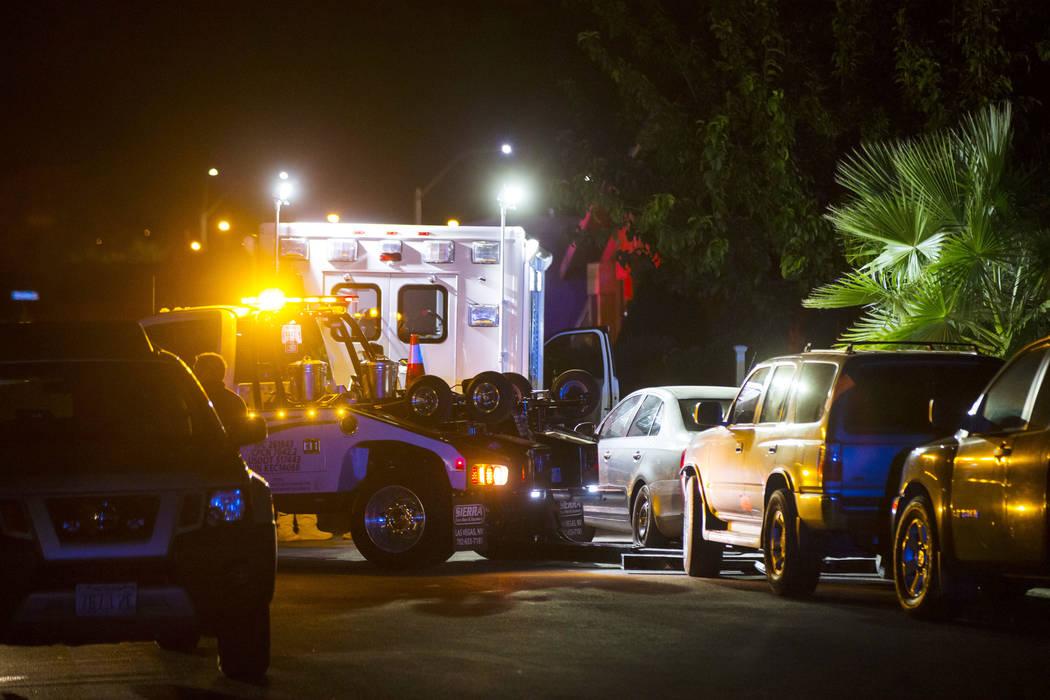 Una grúa se prepara para mover un vehículo que bloquea un camino de entrada mientras la polic ...