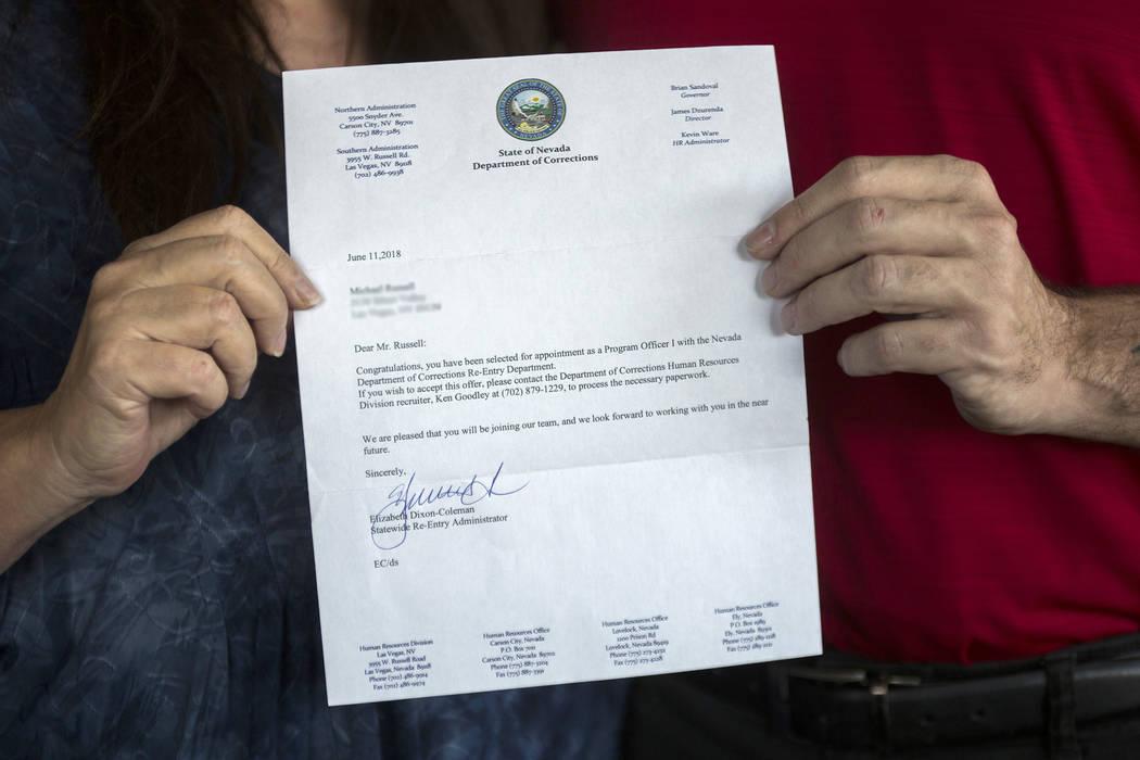 Michael Russell y su madre, Jill Drysdale, sostienen la carta del Departamento de Correcciones ...