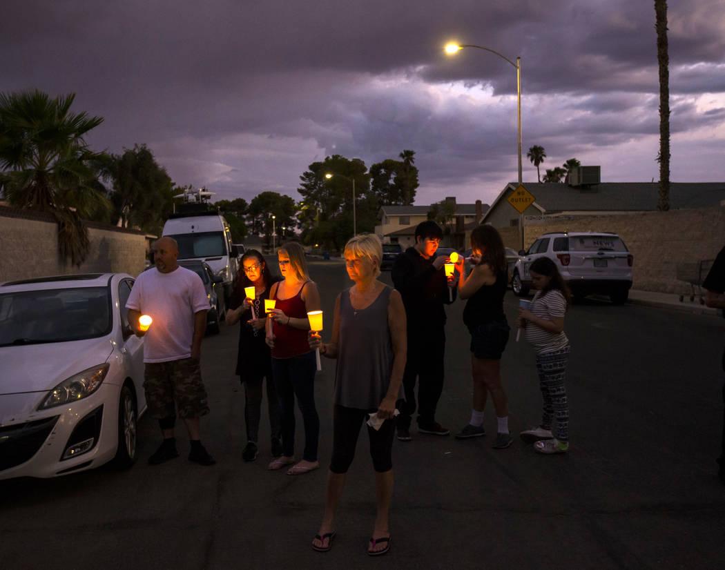 Personas sostienen velas durante un velorio en memoria de Jennifer Ratay afuera de la casa dond ...