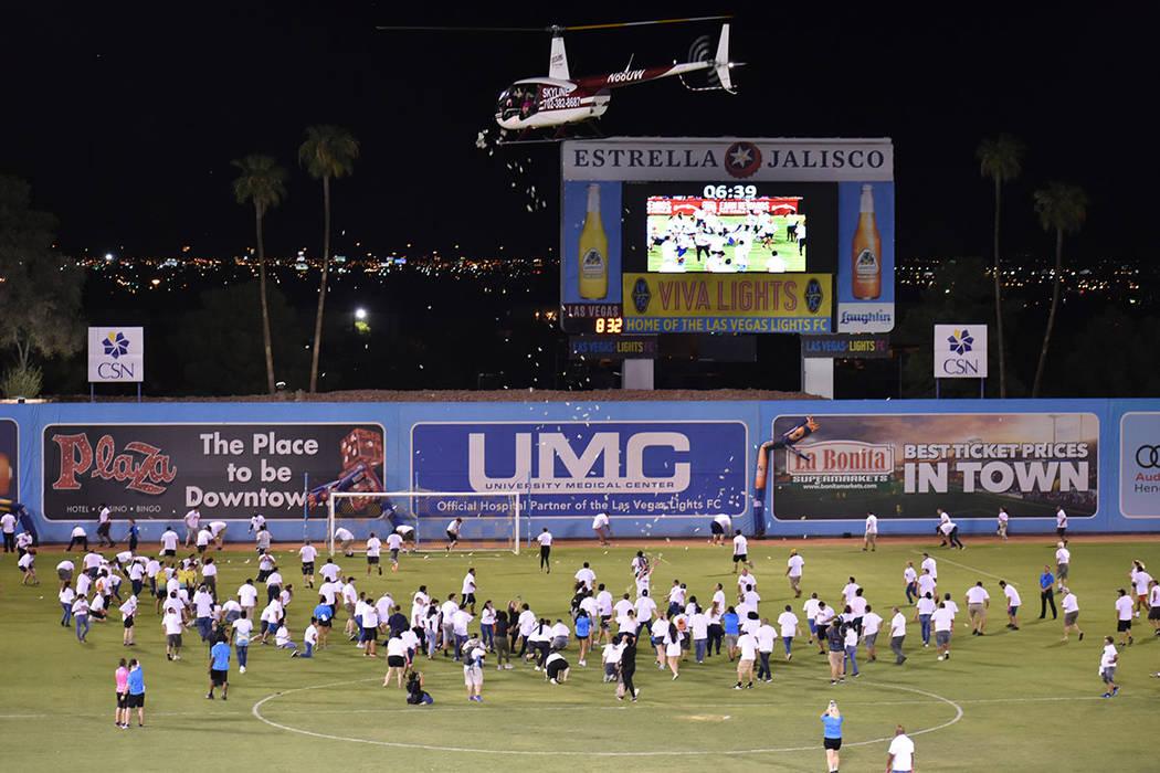 """La mascota """"Cash"""" arrojó dinero desde un helicóptero para 200 aficionados durante el medi ..."""