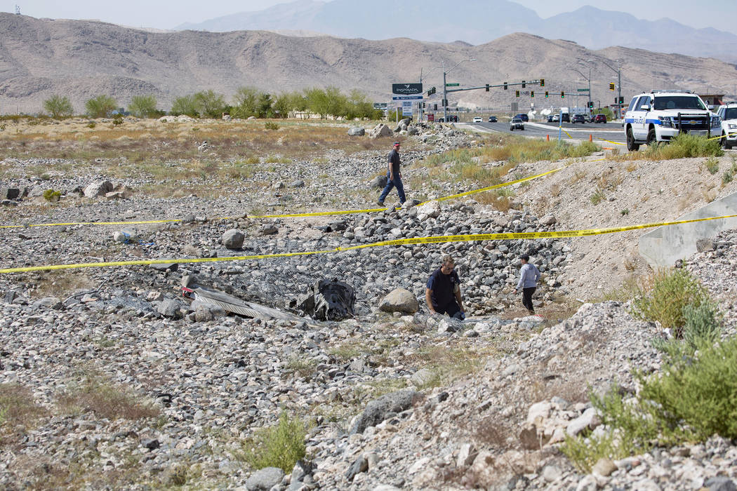 Los empleados de la Administración Federal de Aviación investigan la escena de un accidente a ...