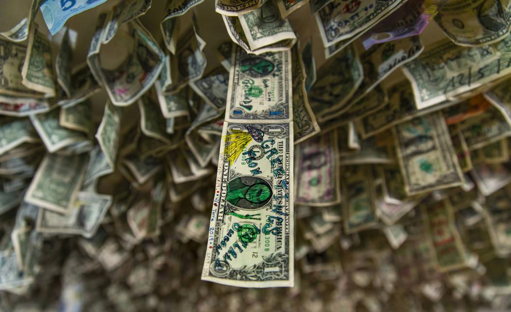 Un billete de un dólar con un dibujo extraterrestre cuelga con muchos otros billetes sobre el ...