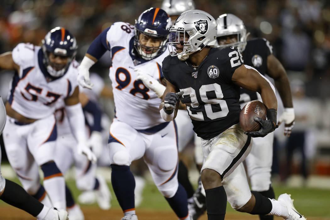 El corredor de los Oakland Raiders, Josh Jacobs, corre con el balón mientras el ala defensiva ...