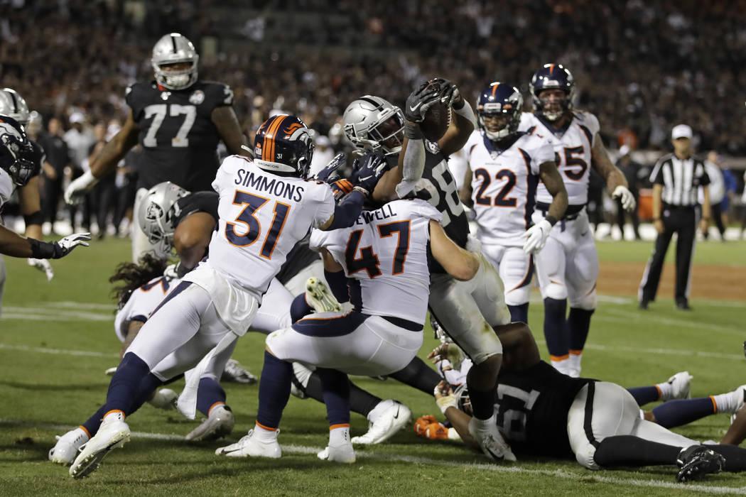 El corredor de los Oakland Raiders, Josh Jacobs (28), anota un touchdown mientras el free safet ...