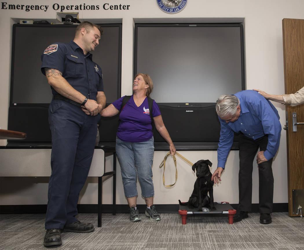 El bombero y paramédico de bomberos de Las Vegas, Tony Brown, a la izquierda, comparte una ris ...
