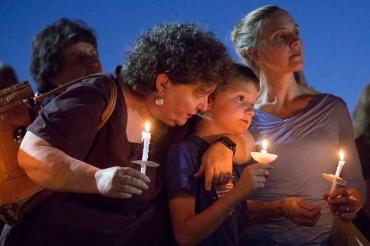 El hermano de Paula Davis, Nathan Davis, en el centro, sostiene una vela con su tía Brenda Mir ...