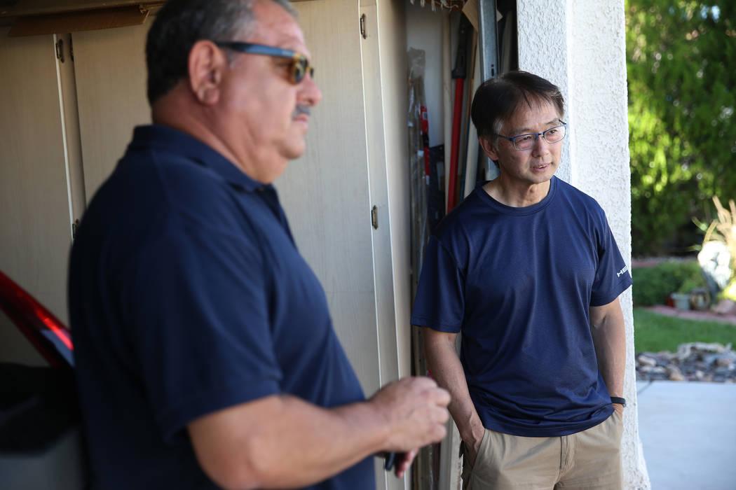 Wayne Niimi, a la izquierda, frente a la casa de su vecino Víctor Padron, muestra en un mapa l ...