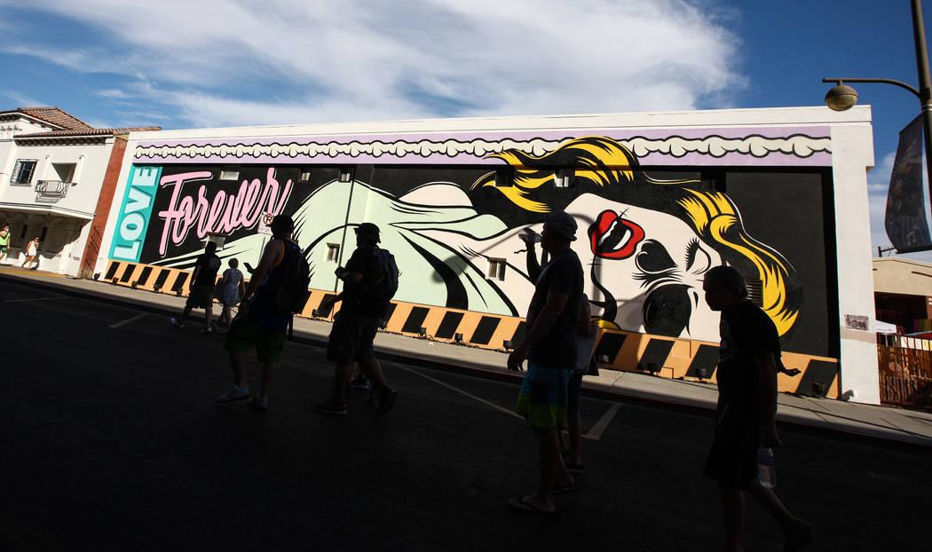 Los asistentes pasan junto a un mural durante el festival Life is Beautiful en el centro de Las ...