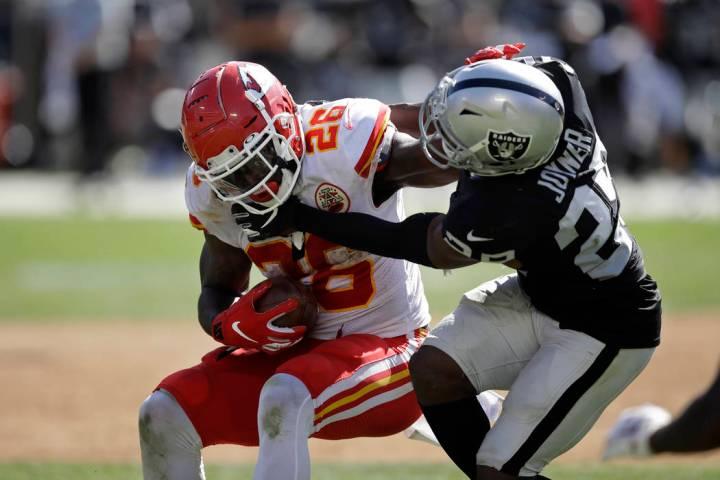 El corredor de los Kansas City Chiefs, Damien Williams, intenta escapar del safety de los Raide ...