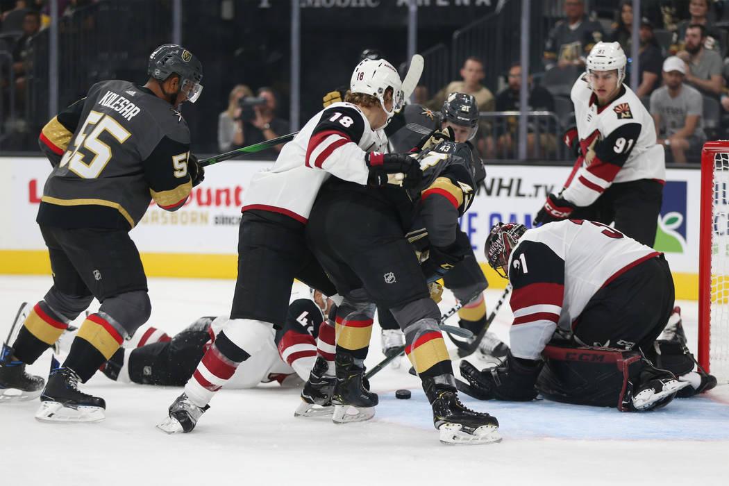 Jugadores luchan por el puck durante el primer tiempo de un juego de hockey de pretemporada de ...
