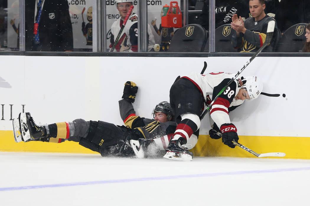 El centro de los Golden Knights de Las Vegas, Cody Glass (9), cae en defensa de los aleros de l ...
