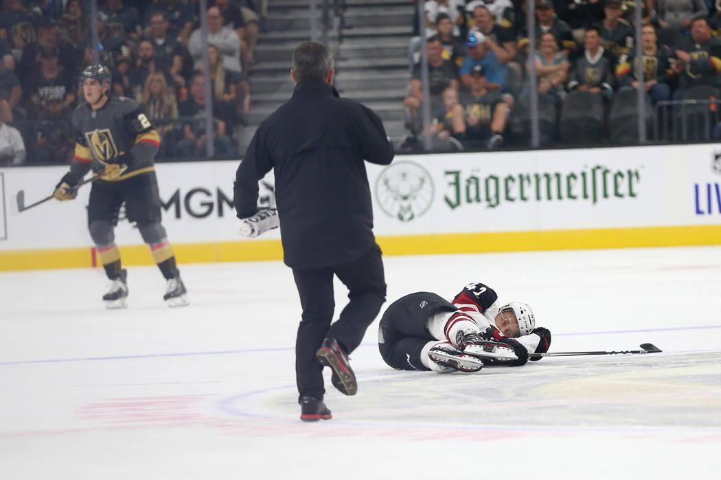 El defensa de los Arizona Coyotes, Aaron Ness (42), cae después de recibir un golpe del ala de ...