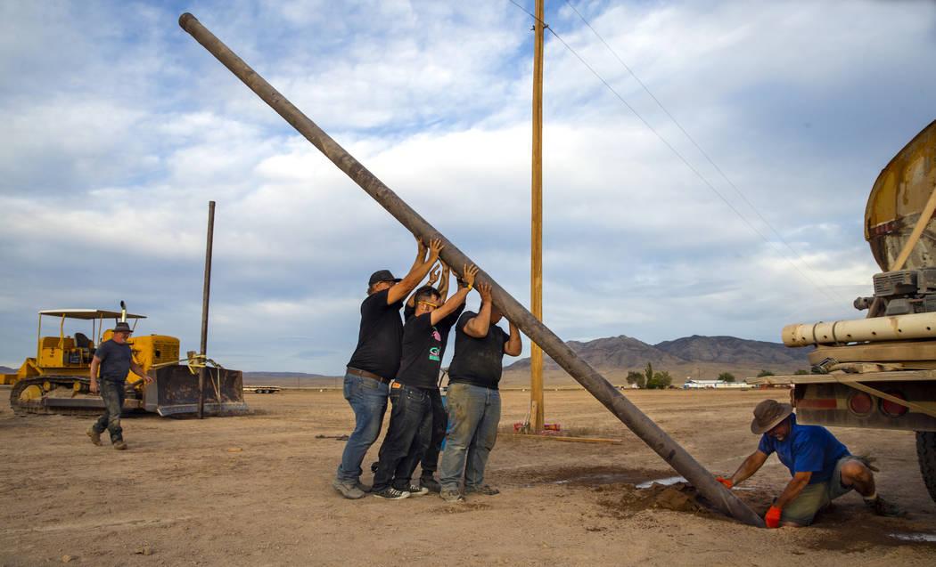 Un equipo trabaja para establecer otro poste para el servicio de internet inalámbrico sobre lo ...