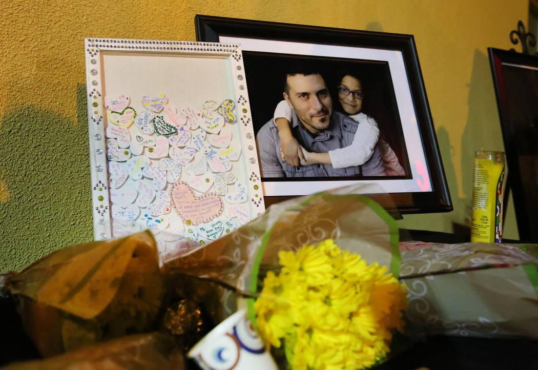 Un ramo de flores yace junto a una fotografía de Mark García y su hija Monet durante un velor ...