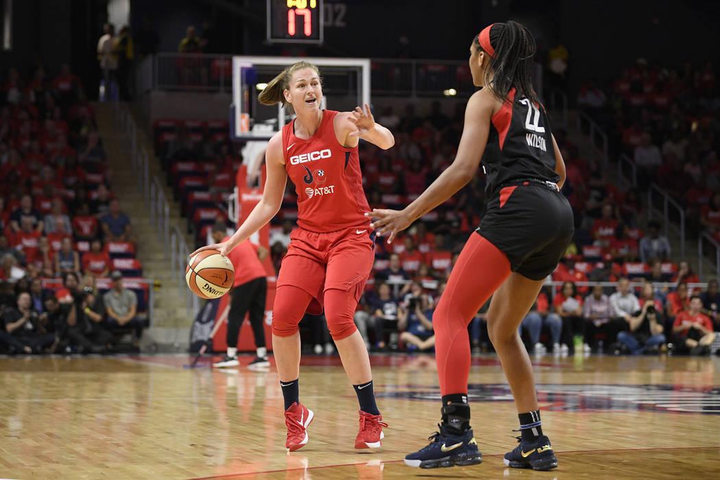 La centro de las Washington Mystics, Emma Meesseman, a la izquierda, bota el balón frente a la ...