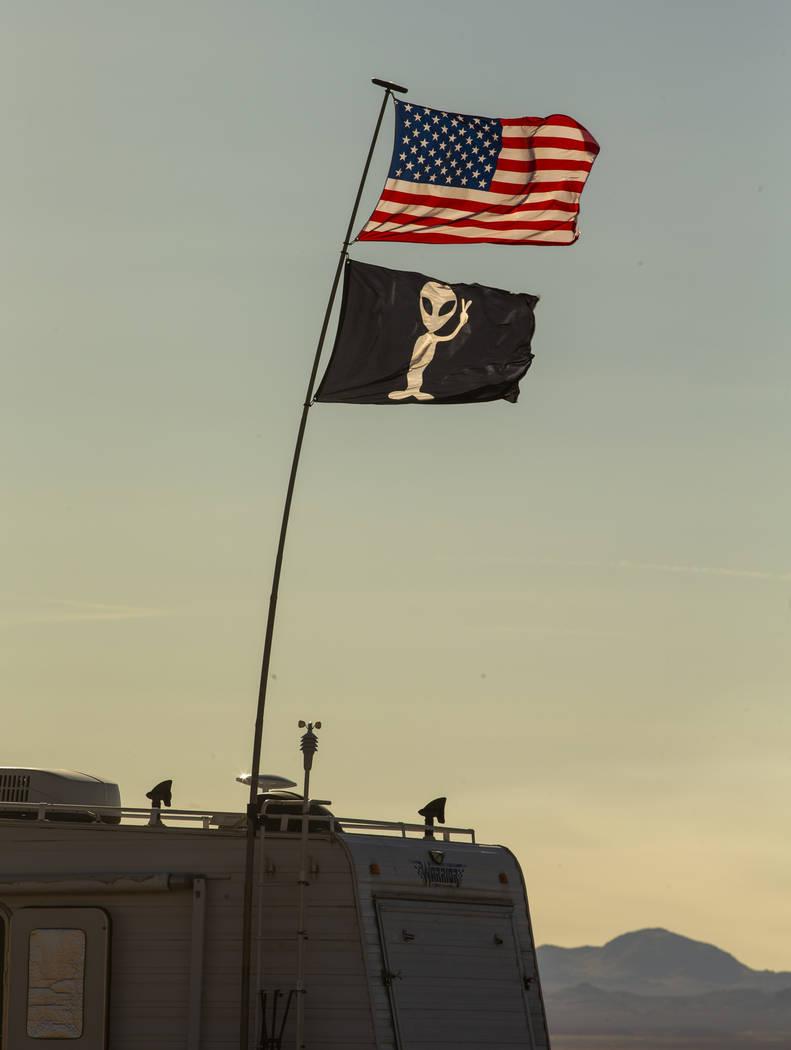 Dos banderas ondean y una casa rodante está estacionada en el desierto mientras se acercan los ...