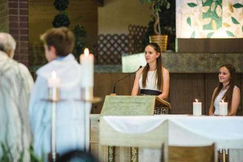Paula Davis, en el centro, habla junto a su hermana durante la boda de sus tíos en la parroqui ...