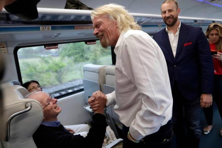 Richard Branson de Virgin Group, saluda a un pasajero mientras viaja en un tren Brightline de M ...