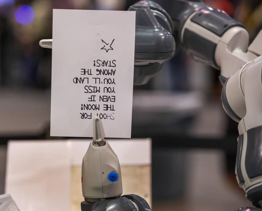 Un robot de Fanuc escribe y dobla una nota para agregarla a los almuerzos escolares para niños ...